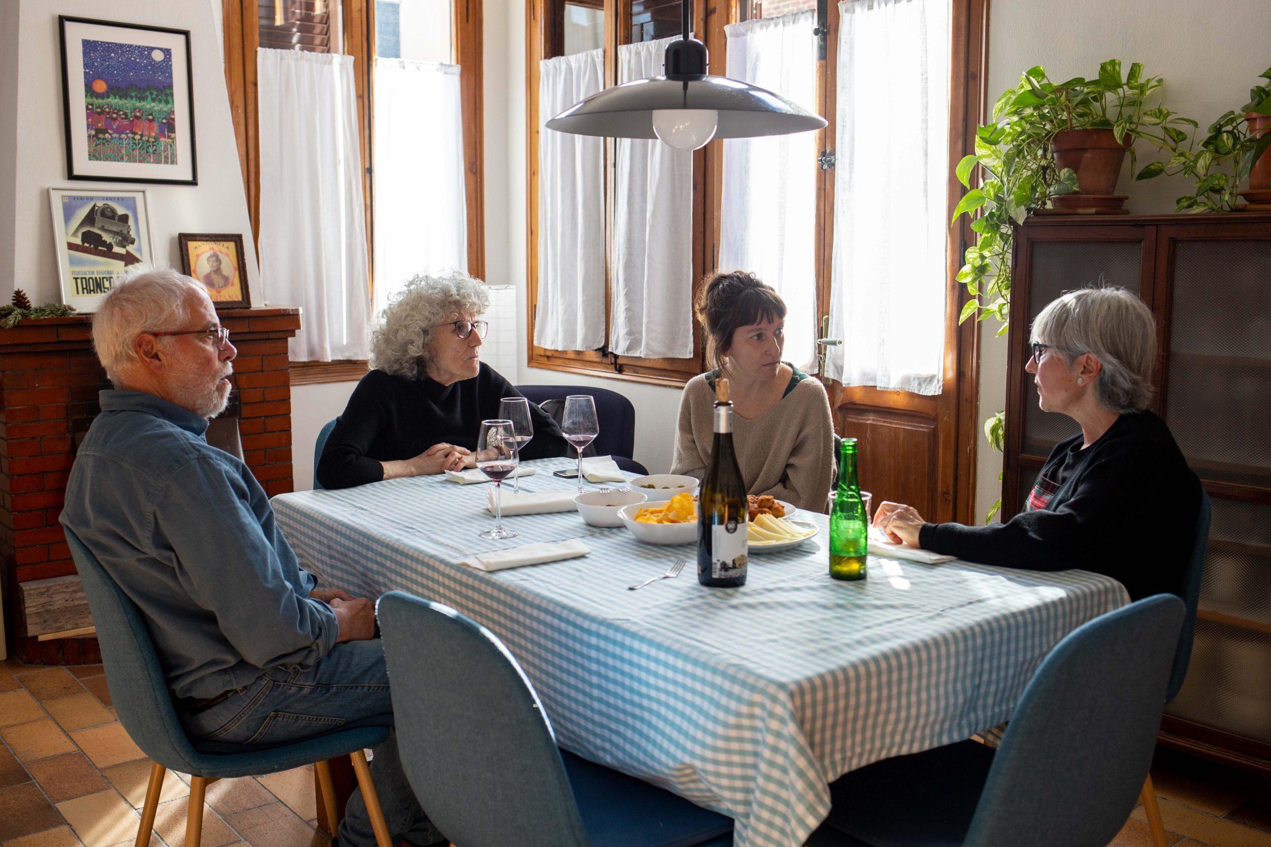 Vista general d'un dinar d'un grup d'amigues assegudes a la taula del menjador de casa
