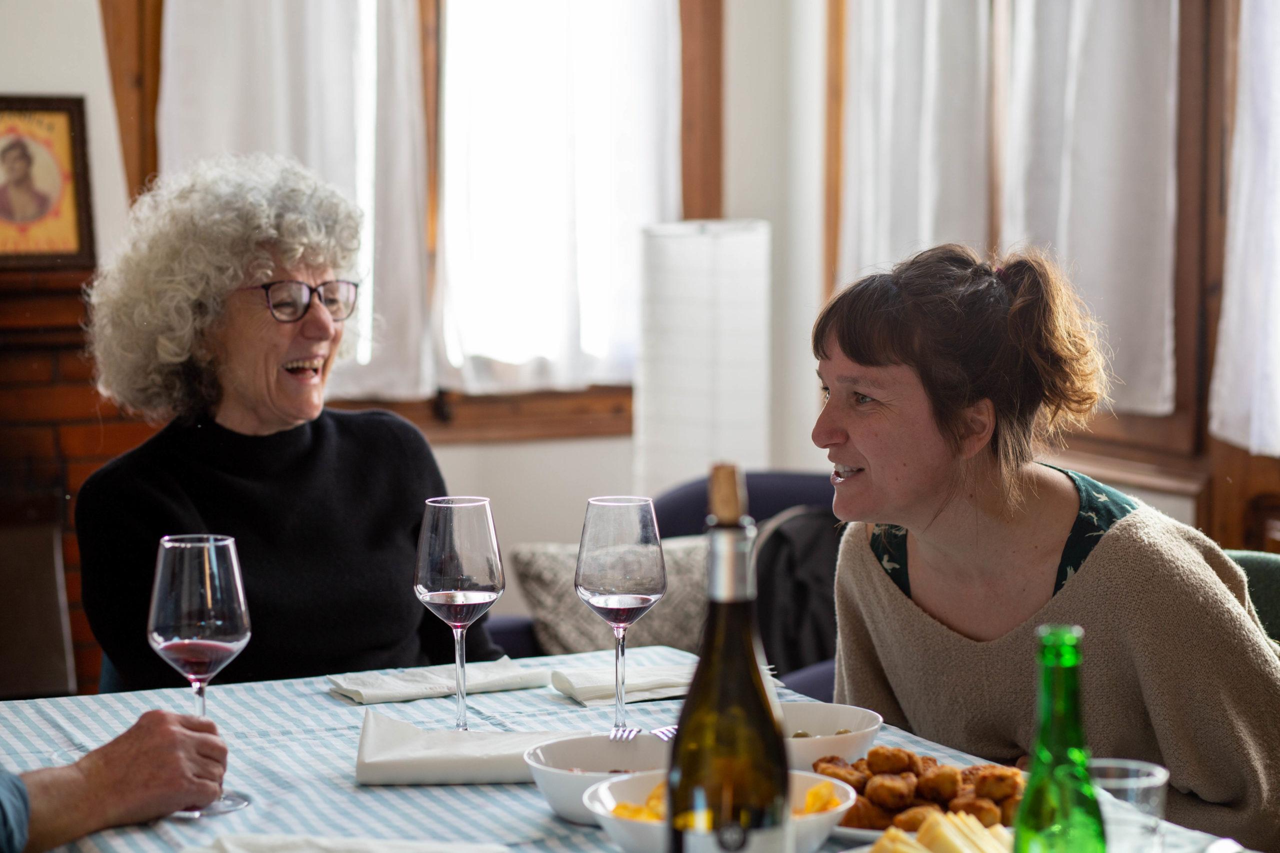 Dues dones rient en un dinar en un menjador de casa