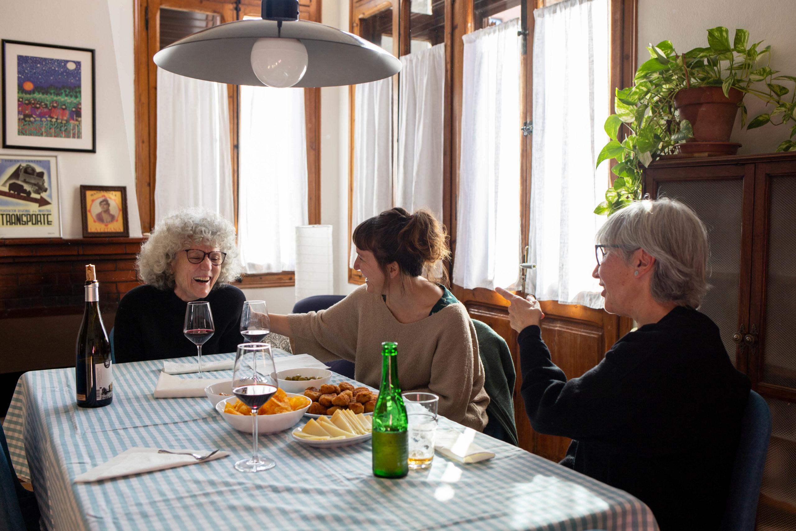 Tres amigues rient en un dinar en un menjador de casa