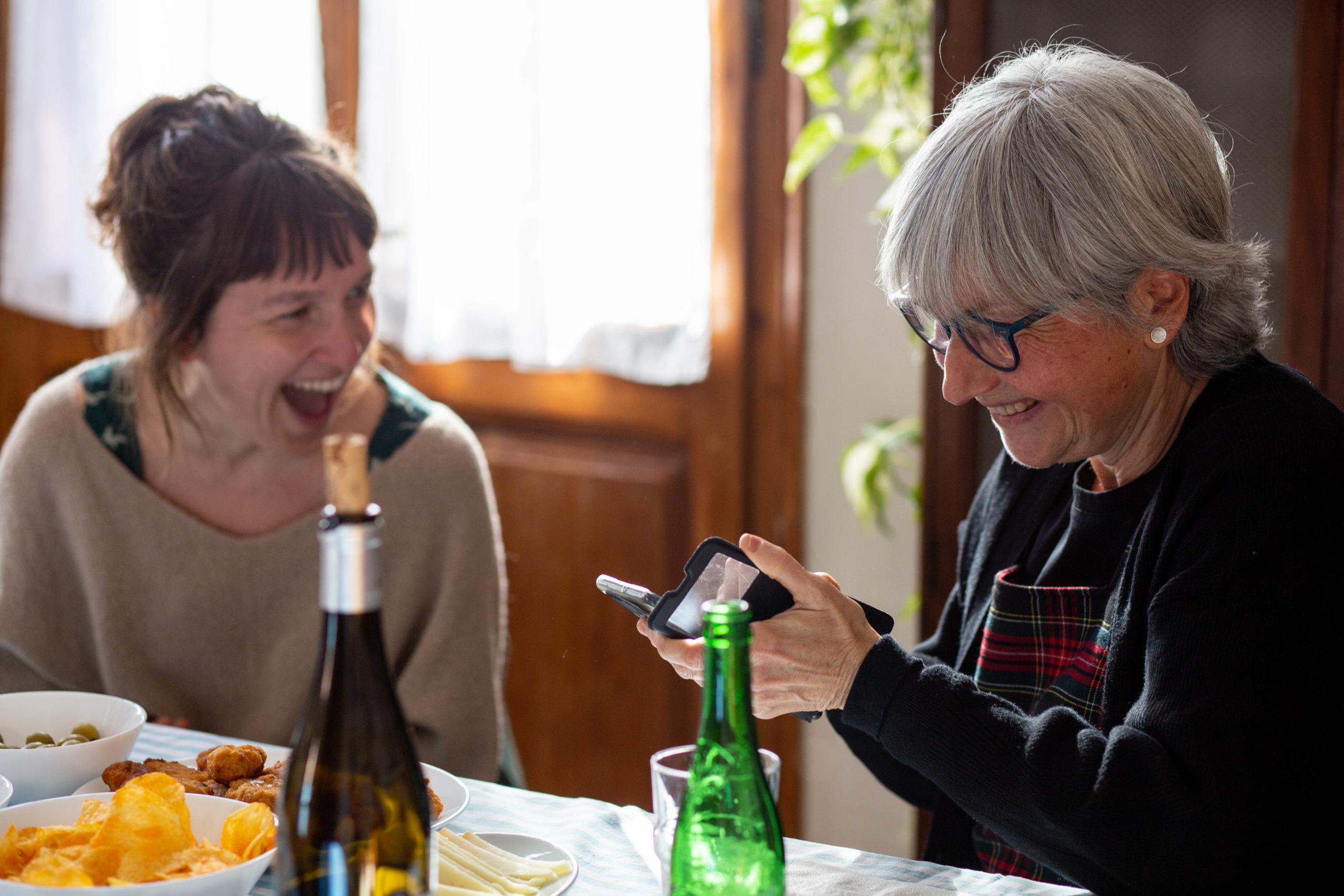 Dues amigues rient en un dinar mentre miren el mòbil en un menjador de casa