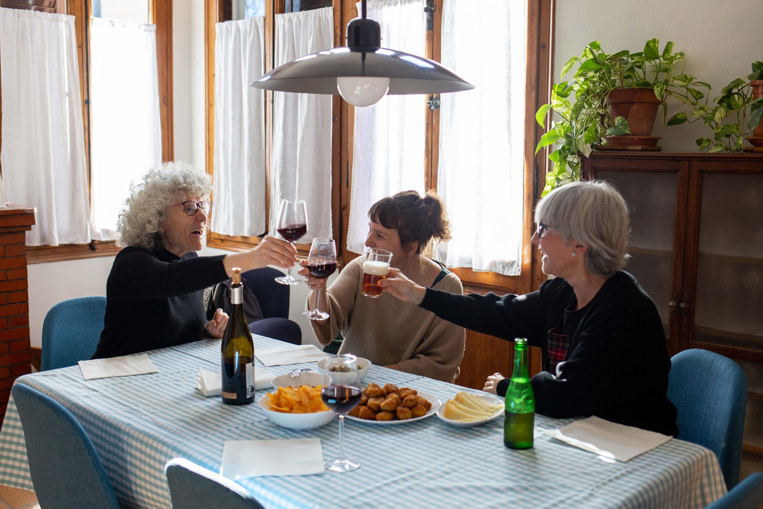 Tres amigues brindant en un dinar al menjador de casa