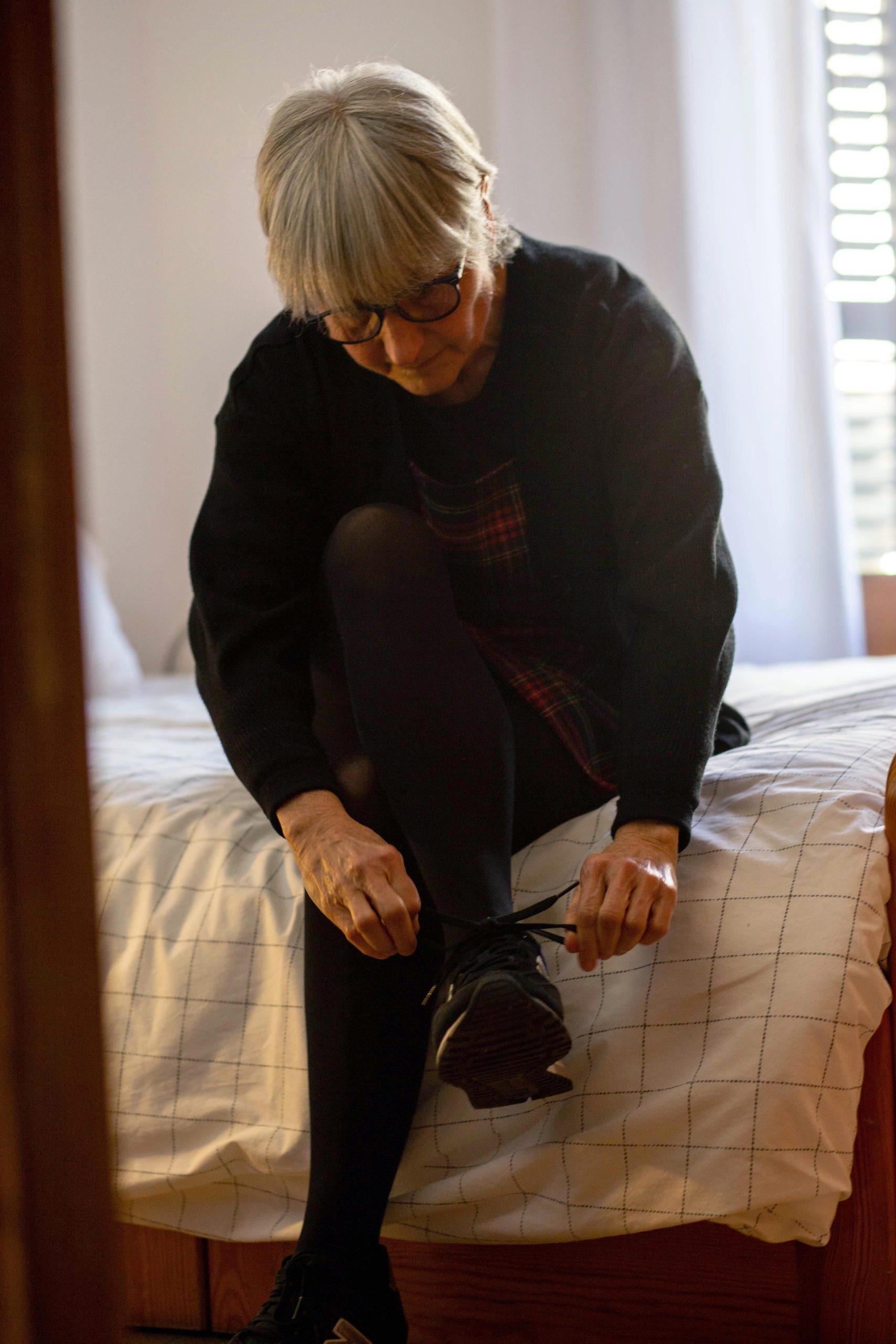Vista general d'una dona cordant-se les sabates asseguda al llit