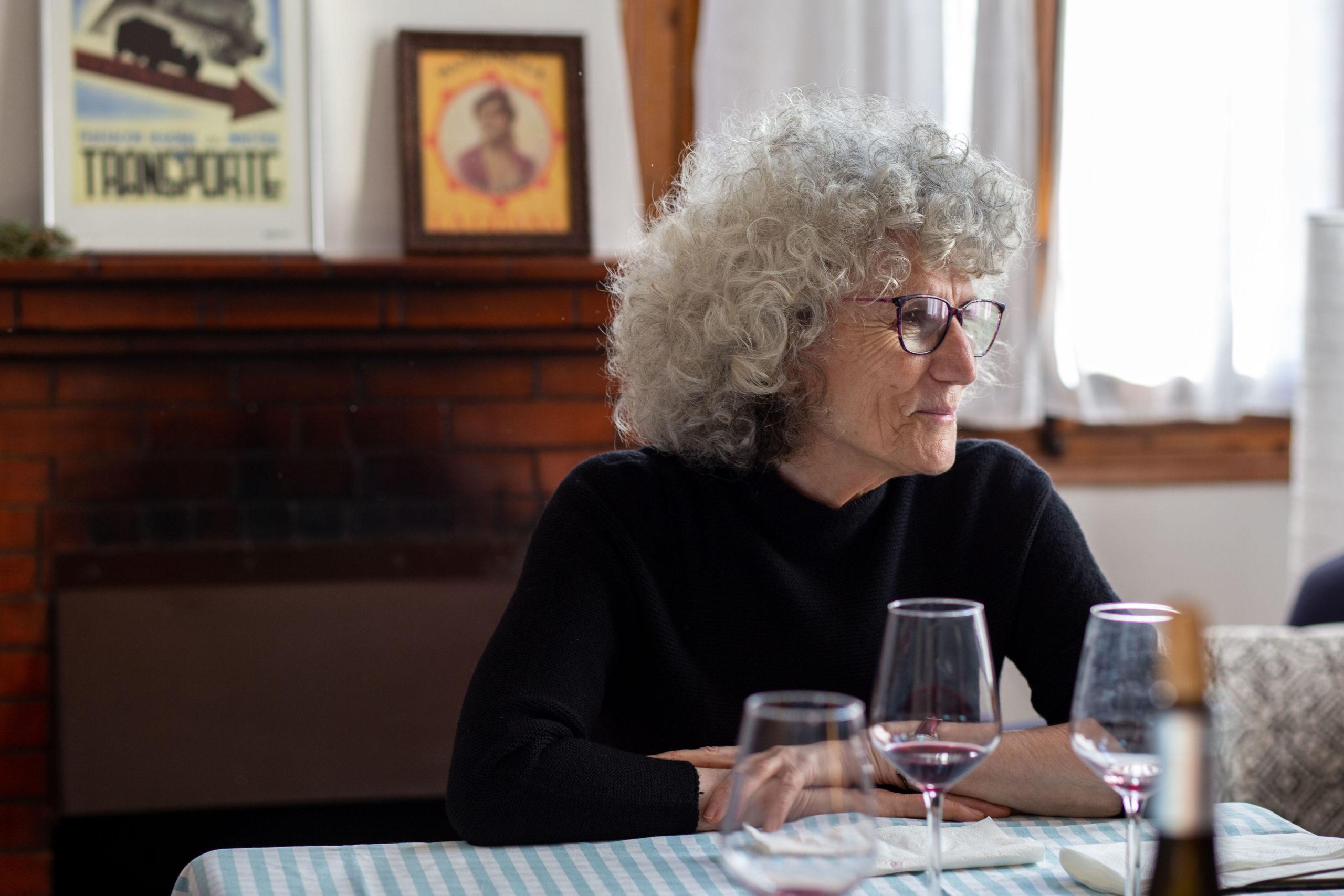 Dona asseguda a la taula en un dinar al menjador de casa