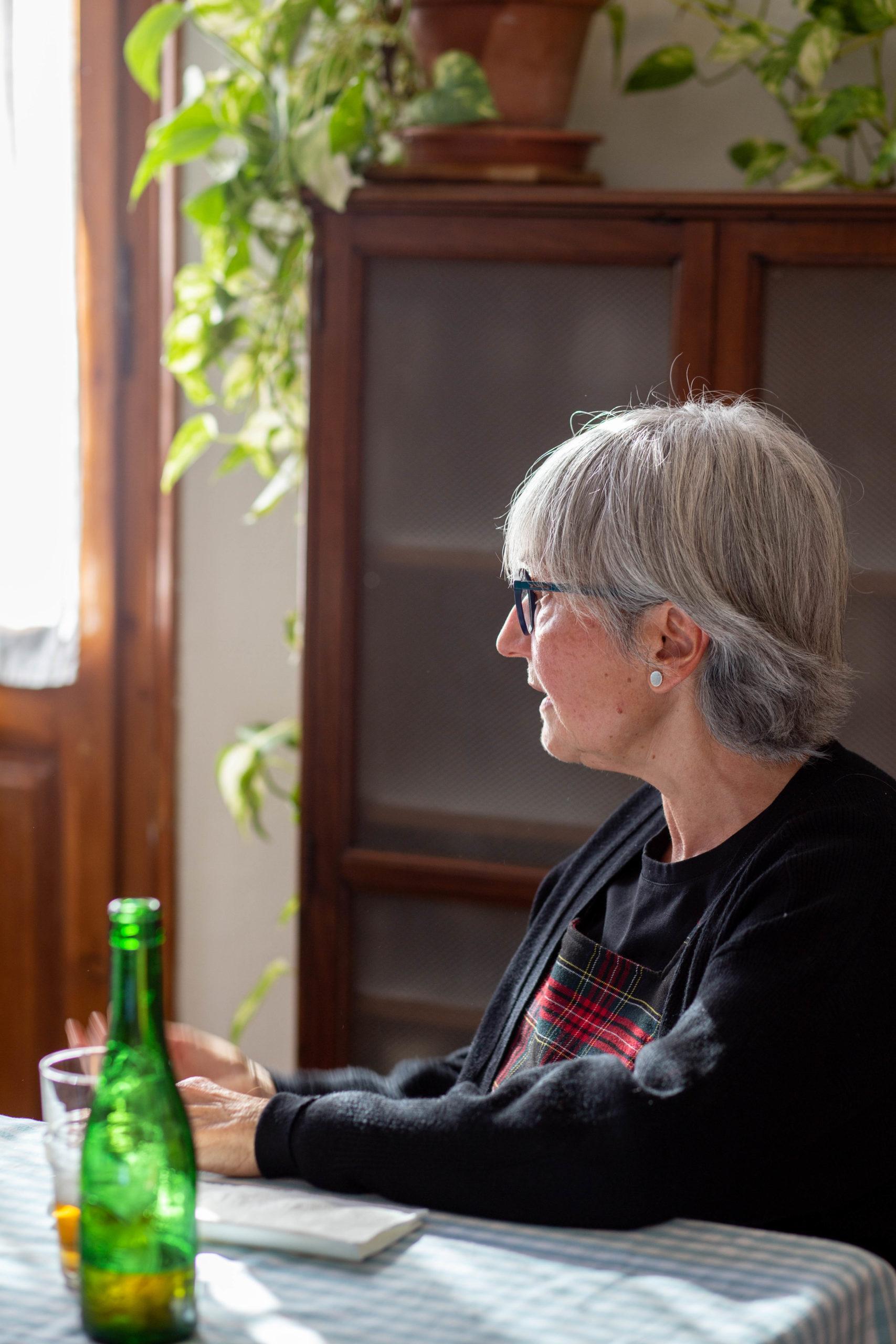 Dona de perfil asseguda en un dinar al menjador de casa