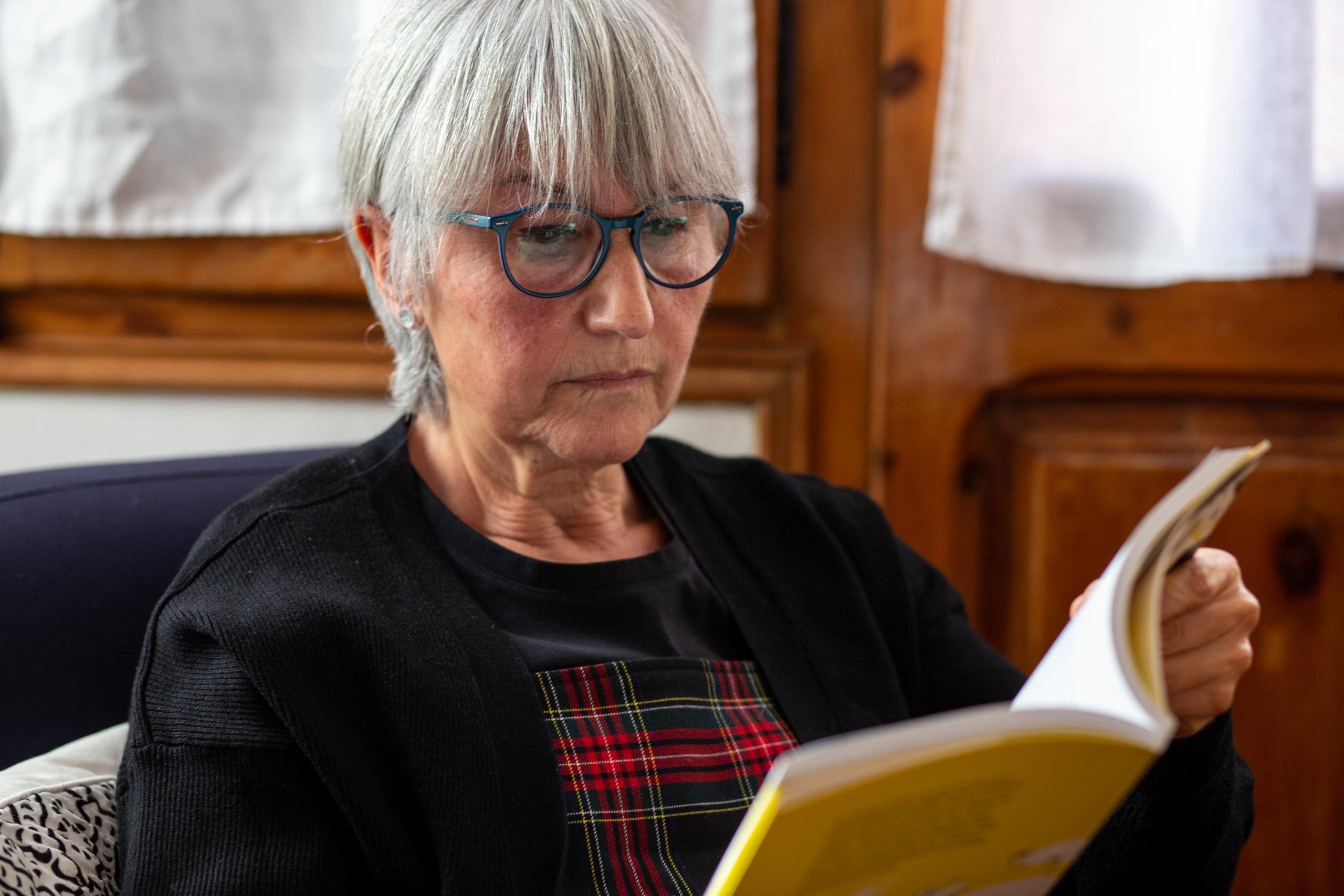 Primer pla d'una dona llegint un llibre asseguda en una butaca