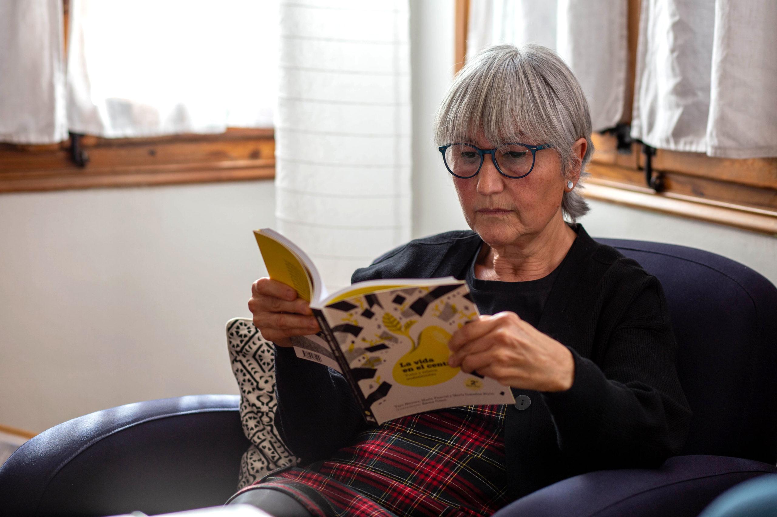 Pla mig d'una dona llegint un llibre asseguda en una butaca