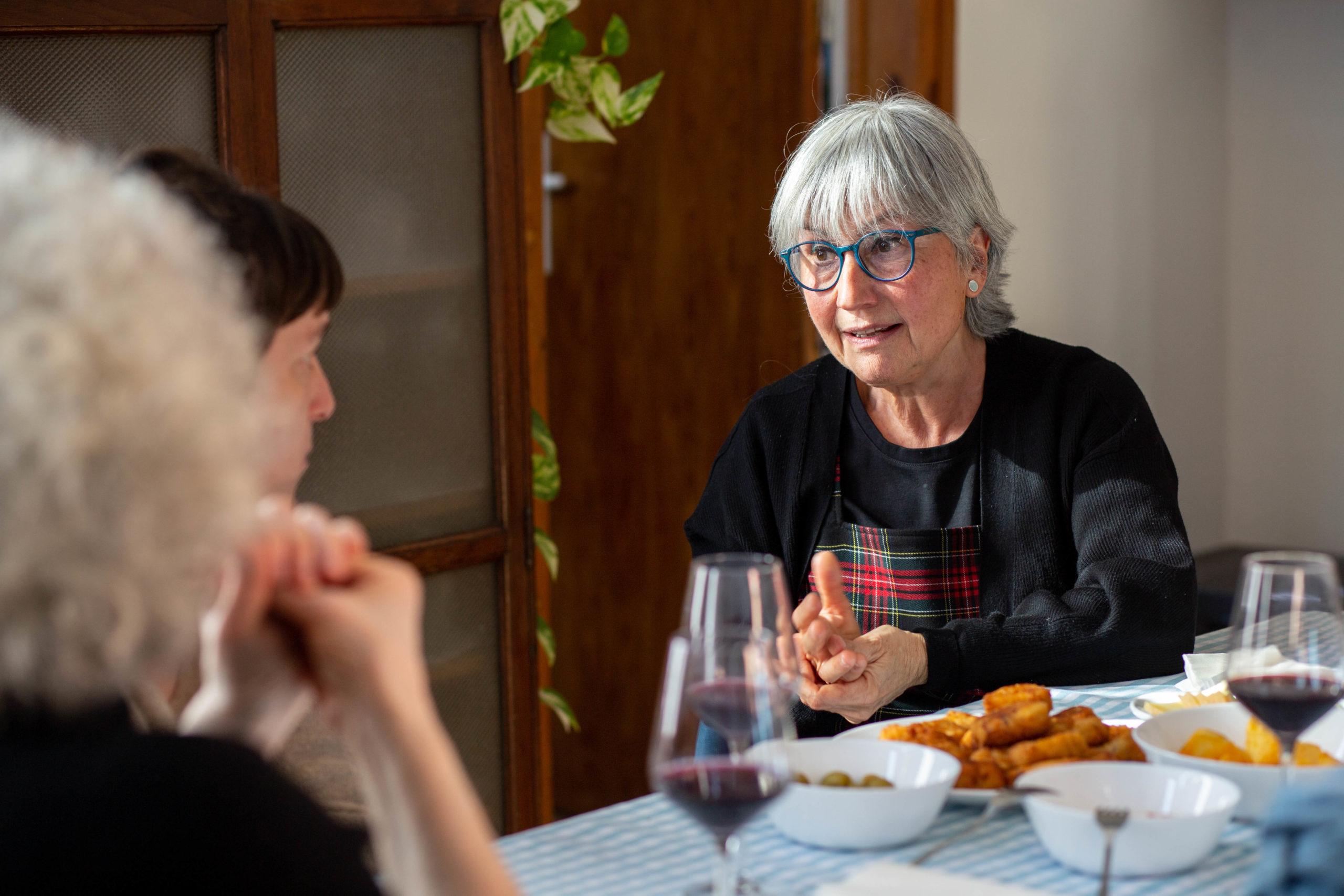 Pla mig dona parlant amb unes amigues en un dinar al menjador de casa