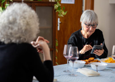 Dona mirant el mòbil amb amigues al menjador