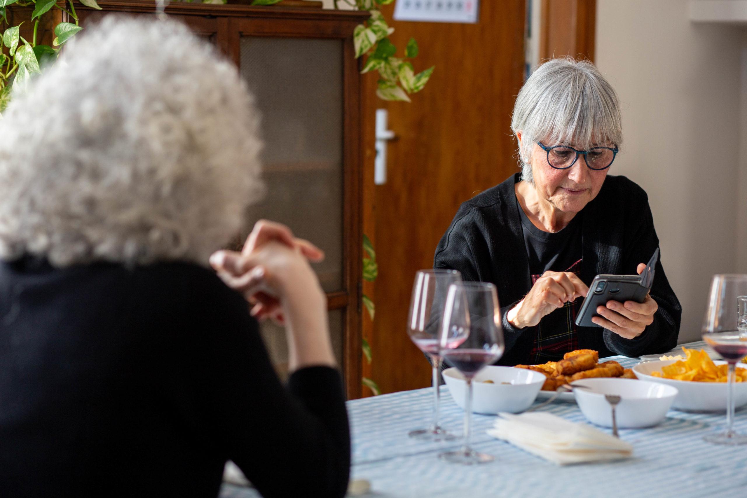 Pla mig d'una dona mirant el mòbil asseguda a la taula del menjador en un dinar