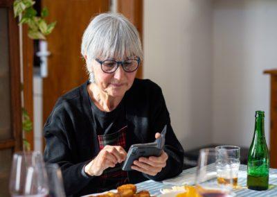 Dona amb mòbil al menjador