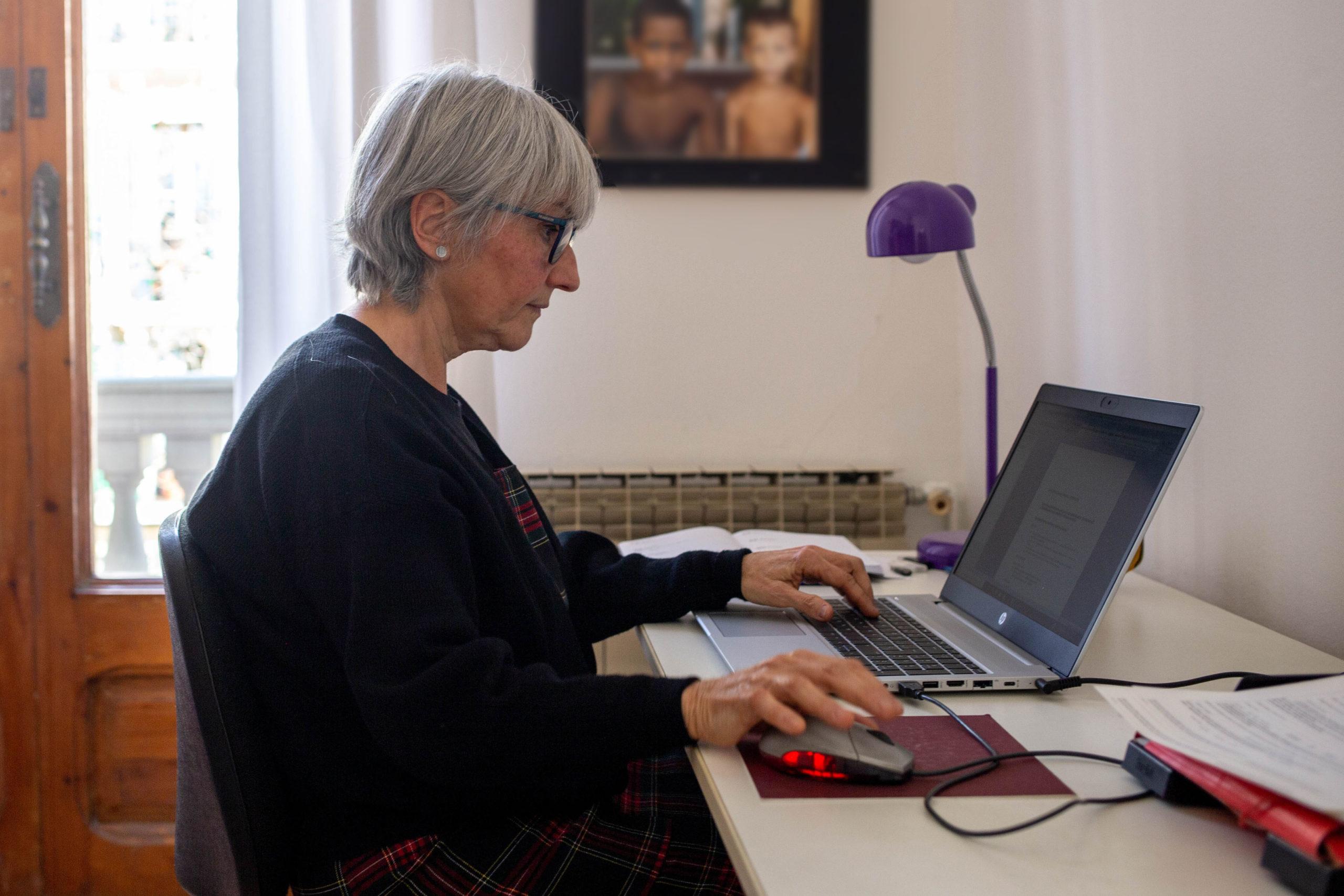 Dona asseguda escrivint a l'ordinador en un despatx