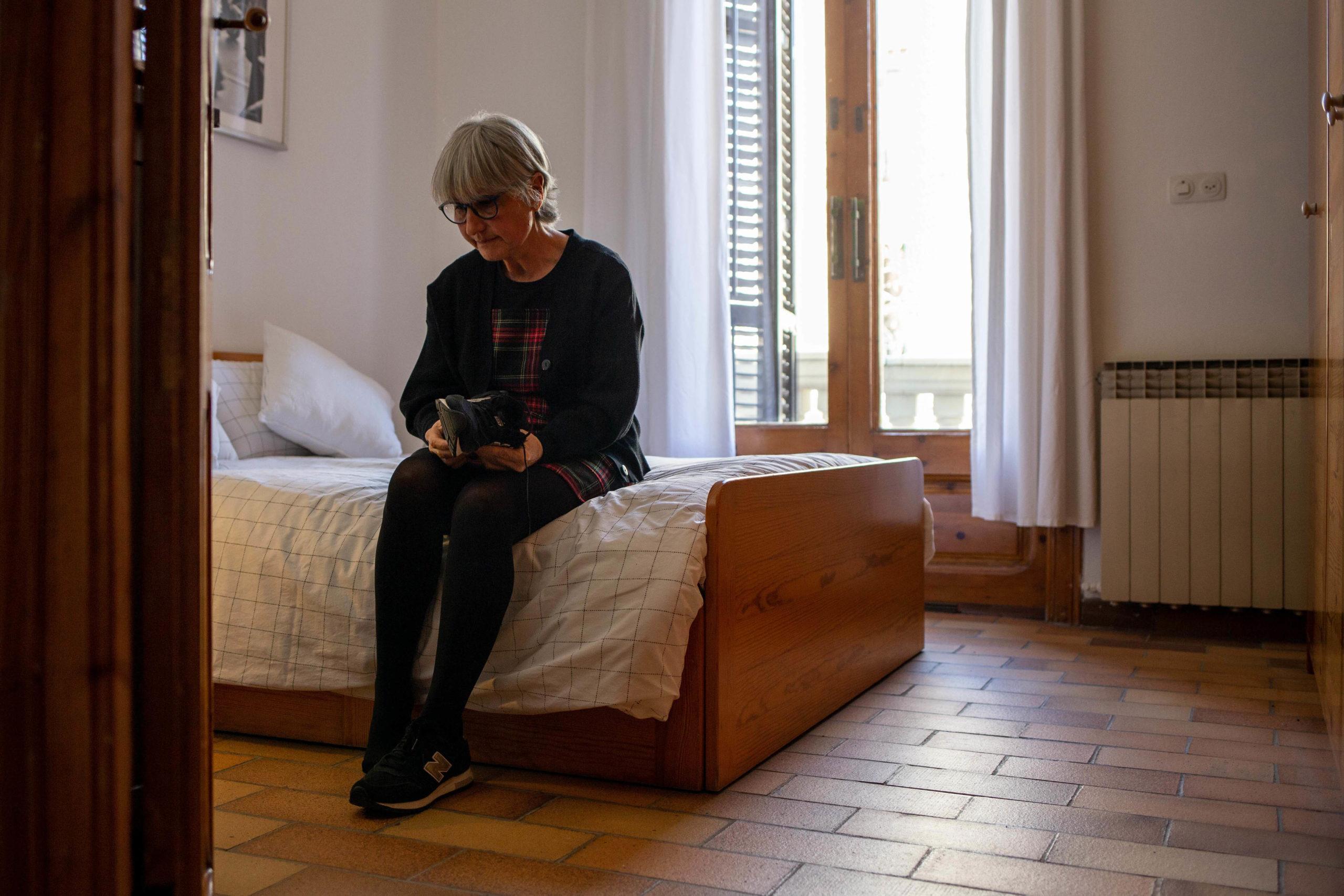 Dona posant-se les sabates al seu dormitori, asseguda damunt del llit