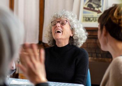 Dona rient amb amigues al menjador 2