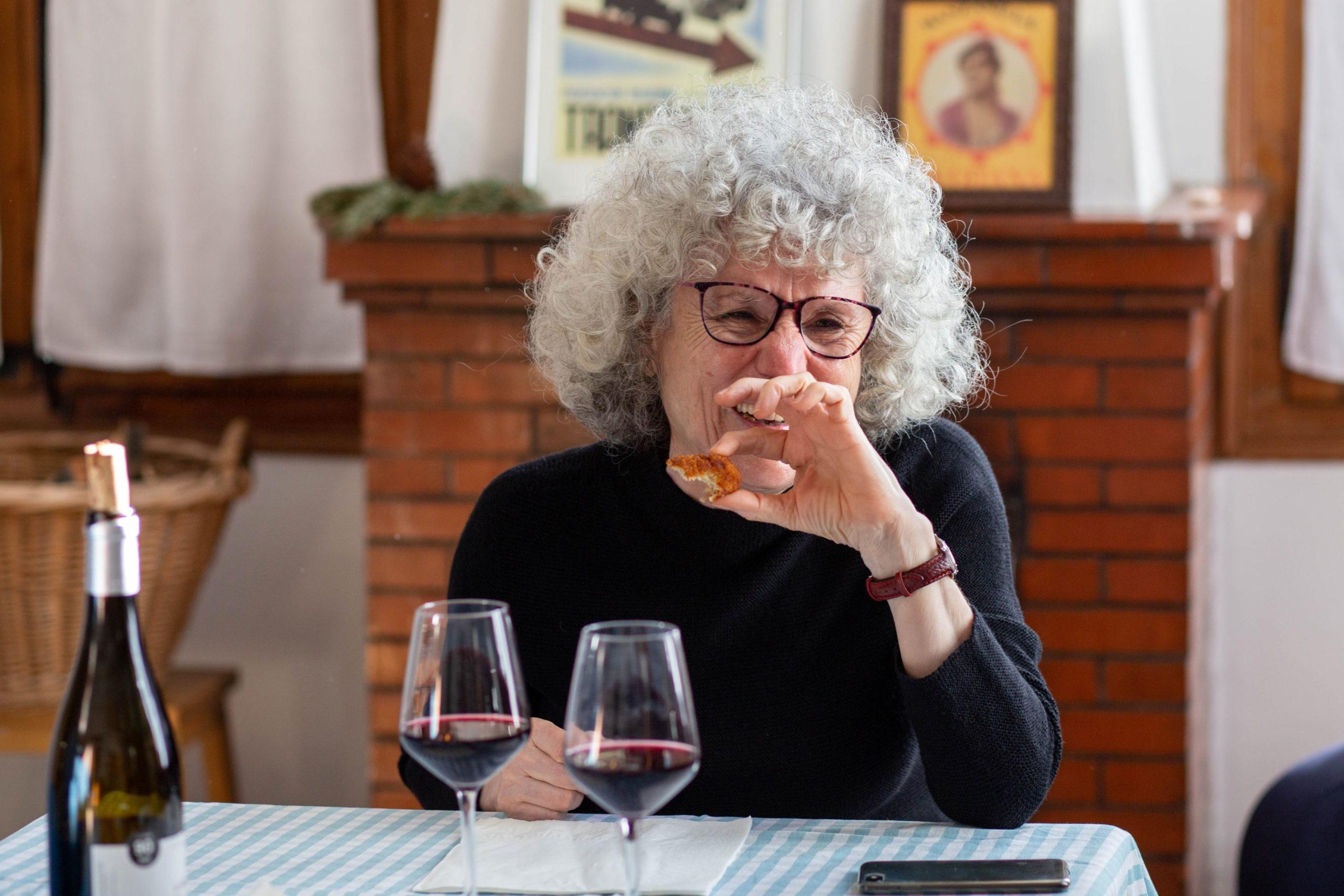 Pla mig dona rient amb unes amigues en un dinar al menjador de casa