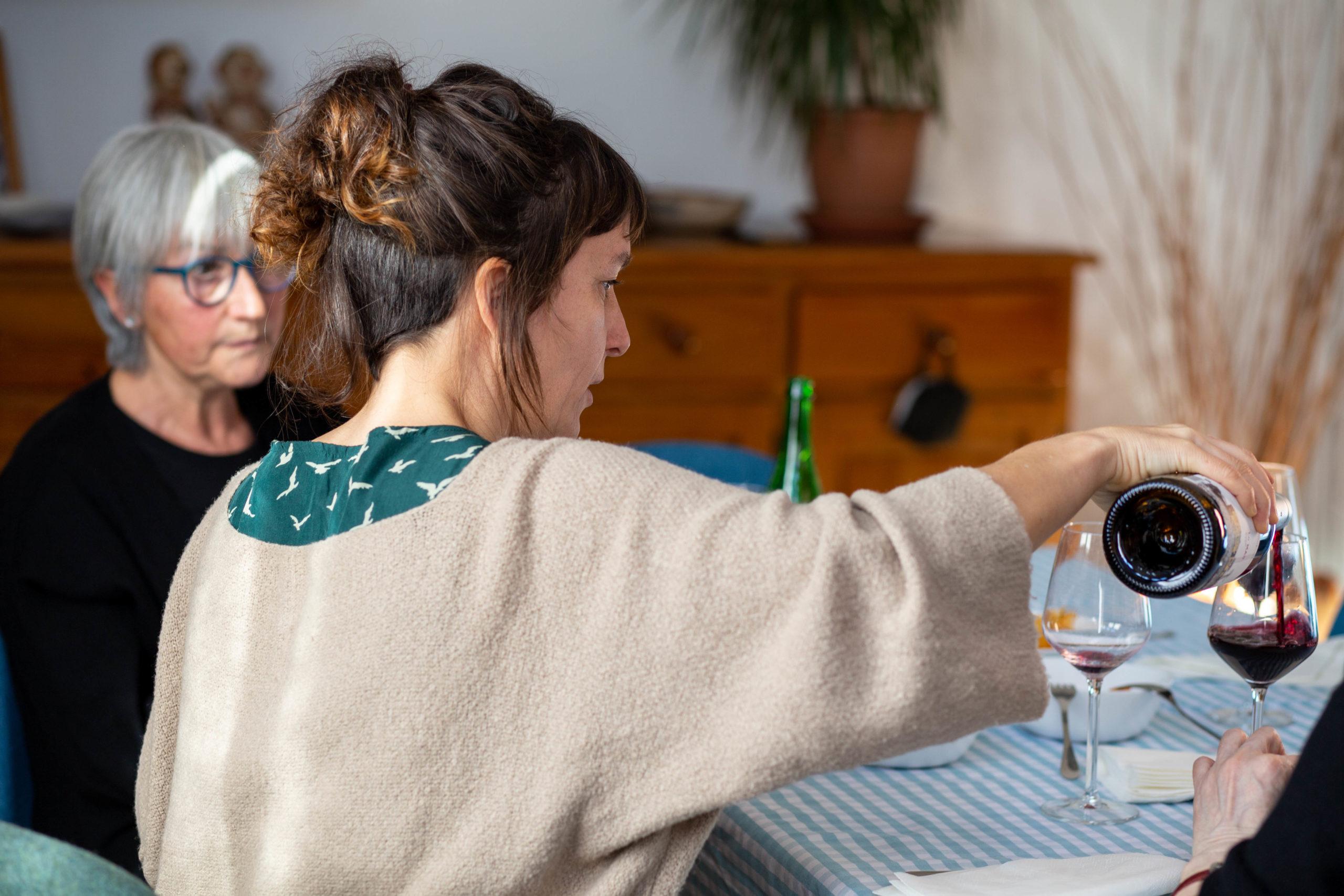 Dona servint una copa de vi en un dinar al menjador de casa