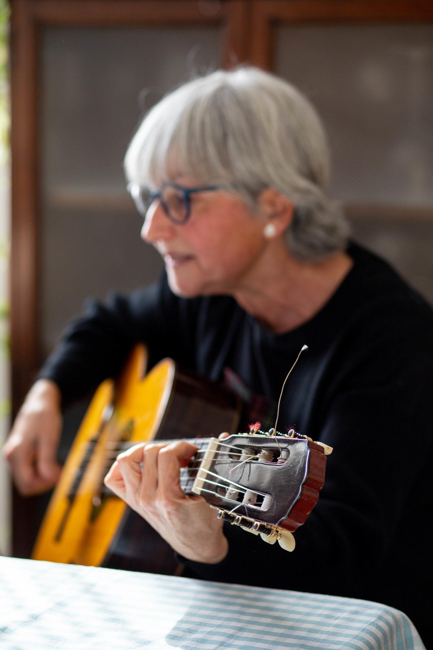 Pla mig d'una dona asseguda tocant la guitarra