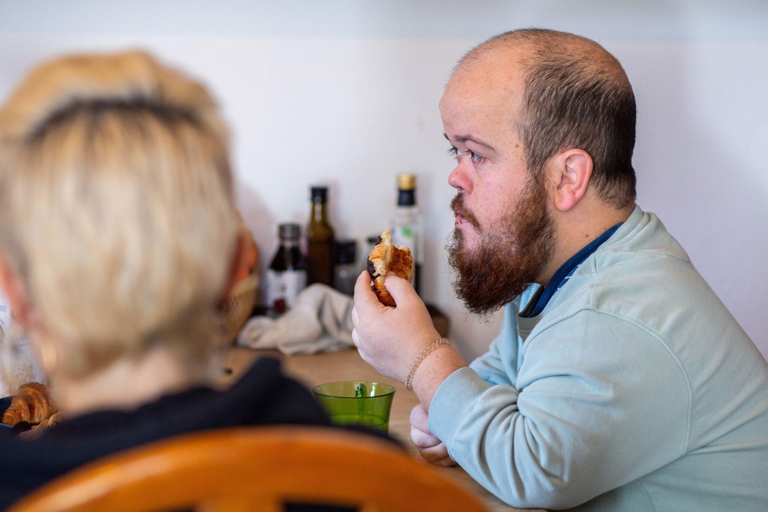 Primer pla d'un noi esmorzant amb companyes de pis