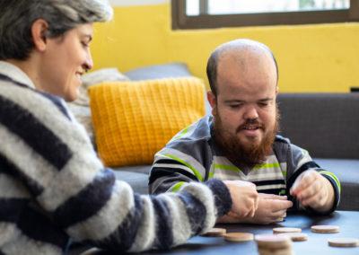 Companyes de pis jugant a un joc de taula al menjador