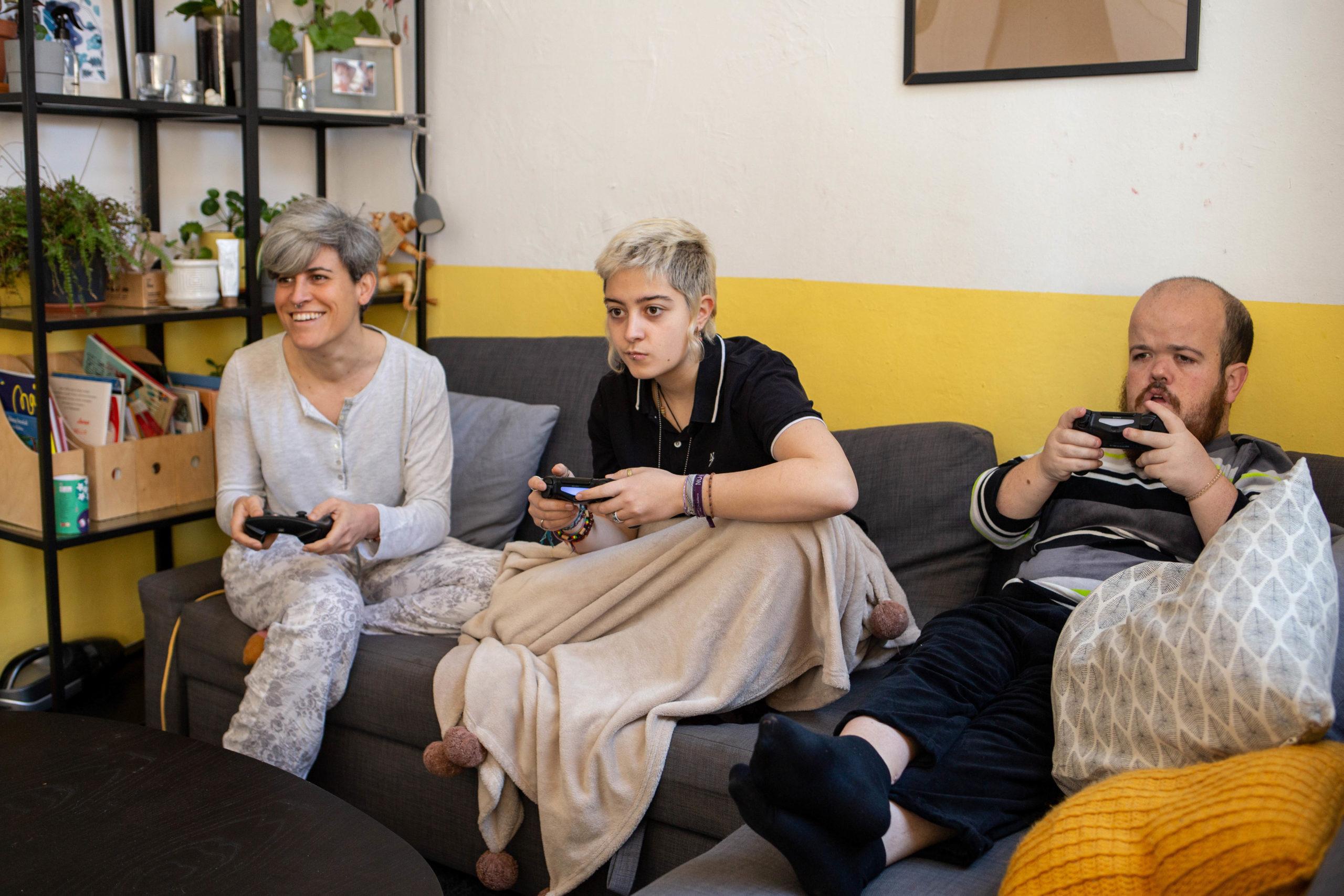 Tres companyes de pis jugant a un videojoc davant de la televisió i assegudes al sofà del menjador