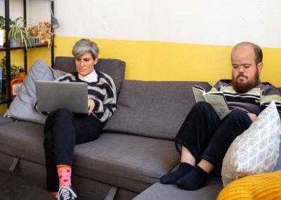 Noia treballant amb l'ordinador i noi llegint un llibre al sofà