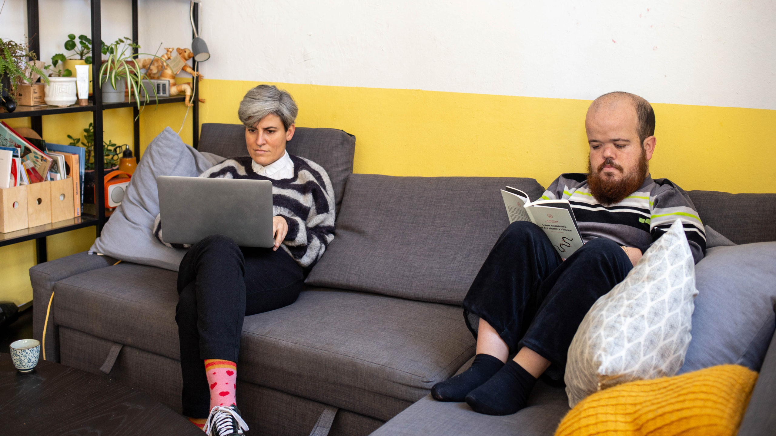 Una noia treballant amb l'ordinador i el seu company de pis llegint un llibre, tots dos asseguts al sofà del menjador
