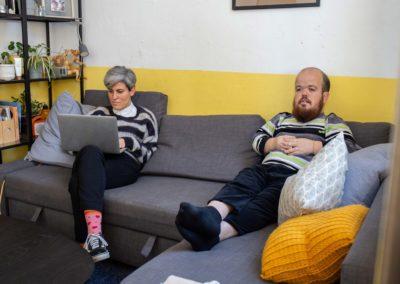 Noia treballant amb l'ordinador i noi veient la televisió al sofà