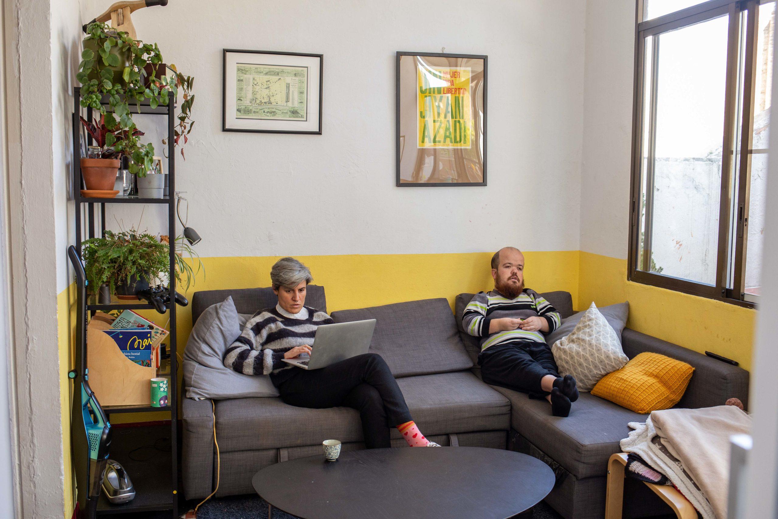 Una noia treballant amb l'ordinador i el seu company de pis mirant la televisió, tots dos asseguts al sofà del menjador