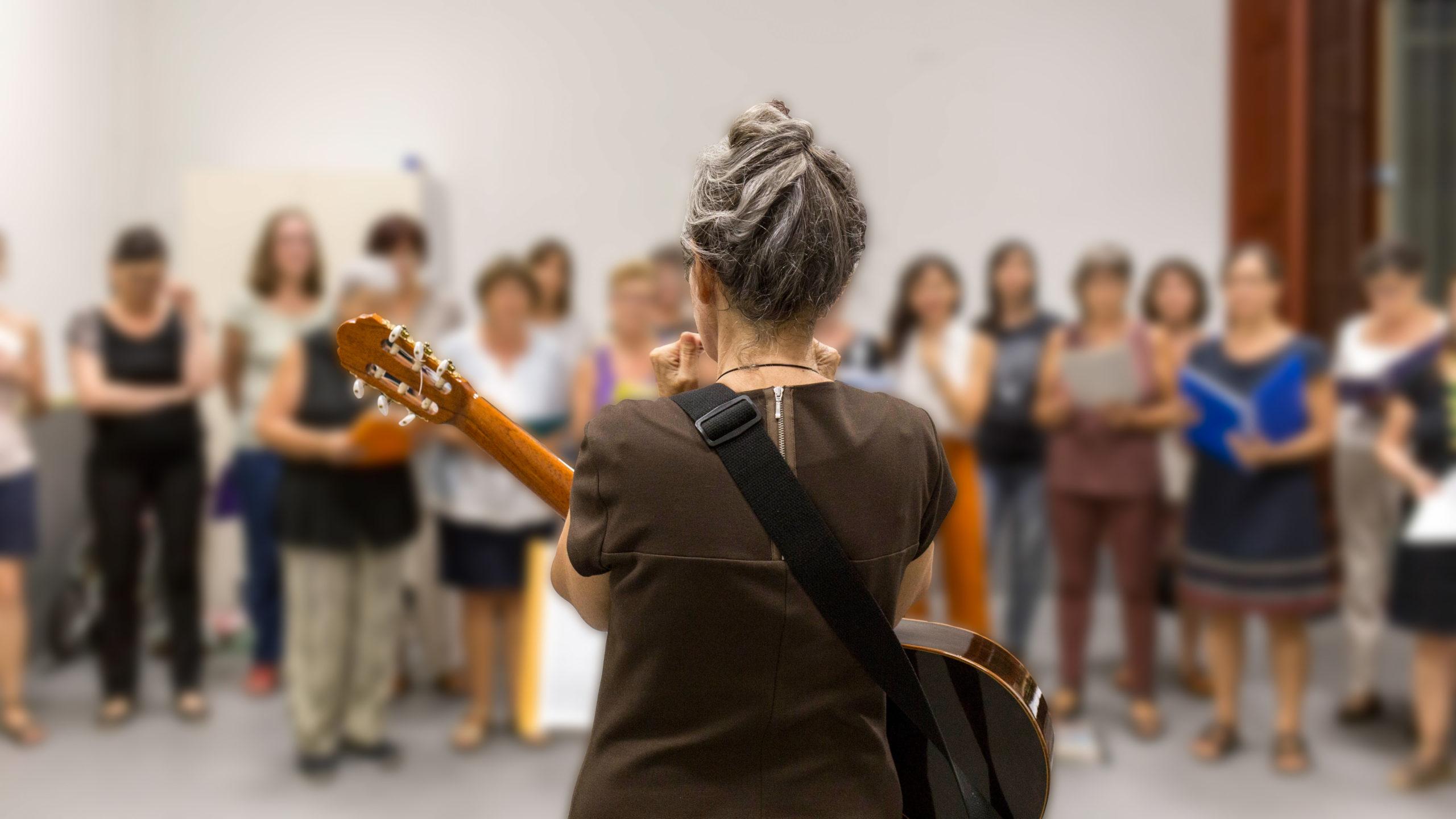 Dona d'esquena tocant la guitarra a la coral