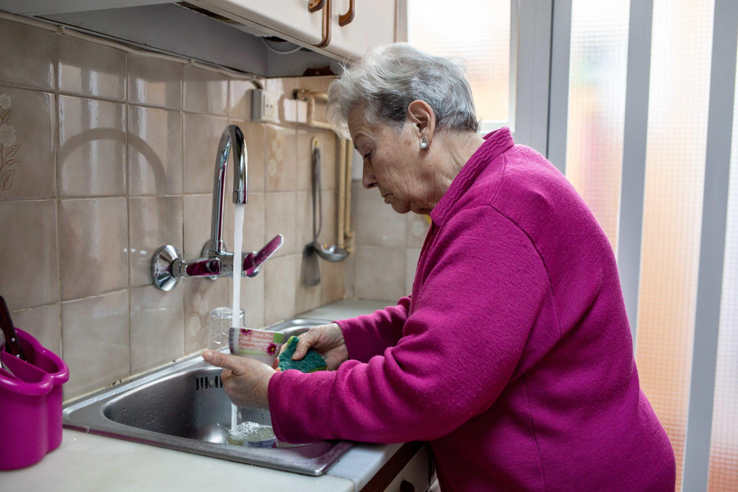 Dona fregant els plats a la cuina
