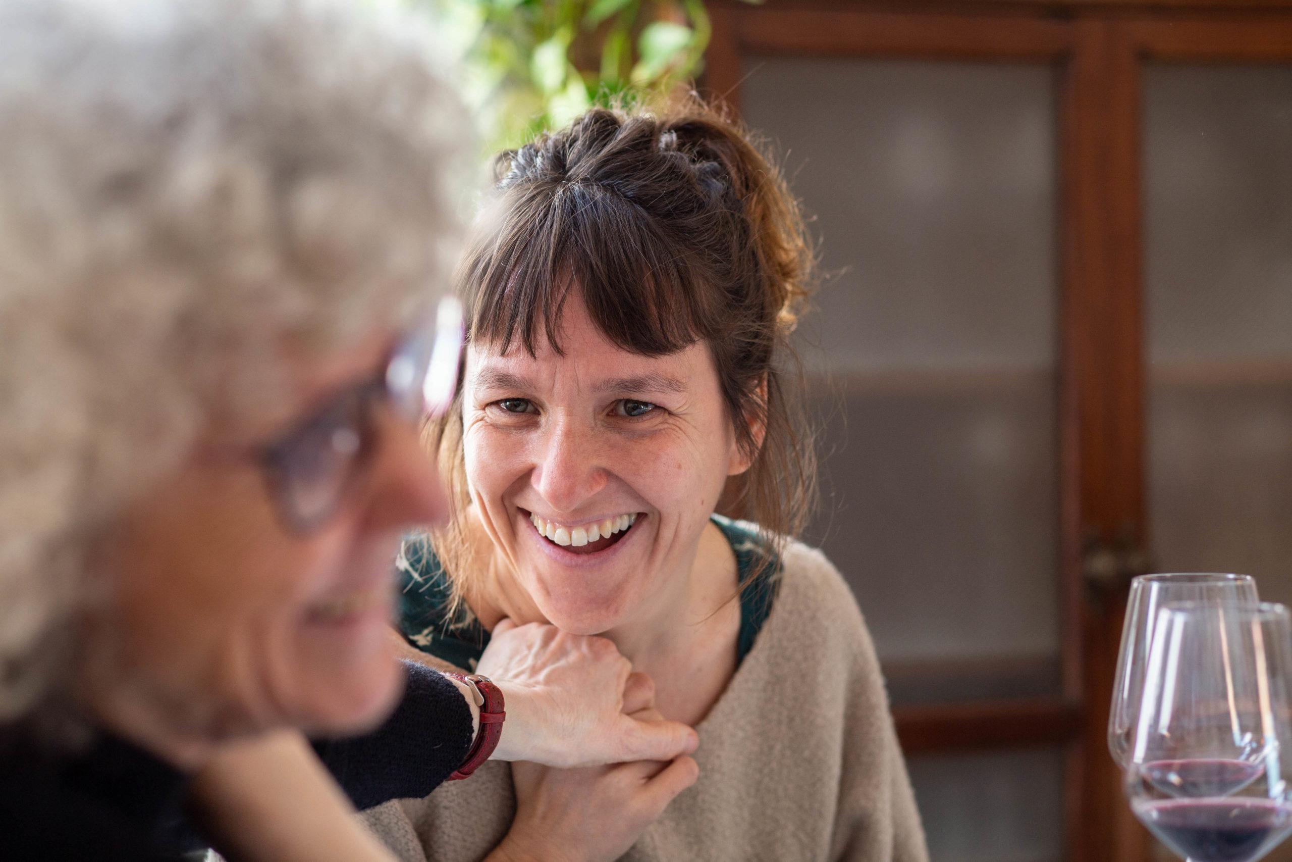 Dues dones agafades de la mà en un dinar al menjador de casa