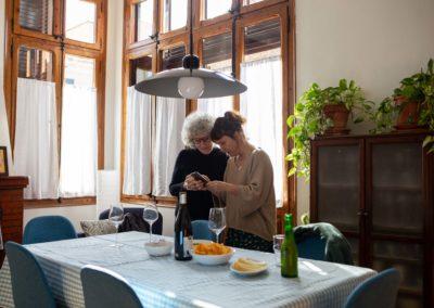 Vista general de dues dones mirant el mòbil al menjador de casa