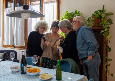 Vista general d'un grup d'amigues mirant el mòbil juntes al menjador de casa