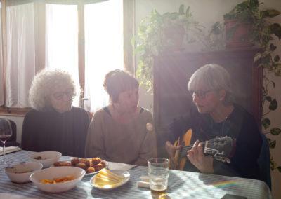 Tres amigues tocant la guitarra i rient al menjador de casa amb el sol entrant per la finestra