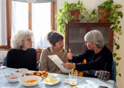 Tres amigues tocant la guitarra al menjador de casa