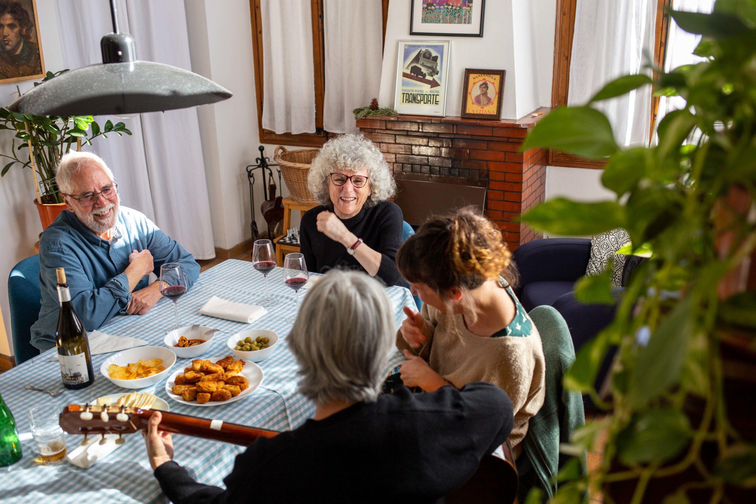Grup d'amigues tocant la guitarra i rient al menjador de casa