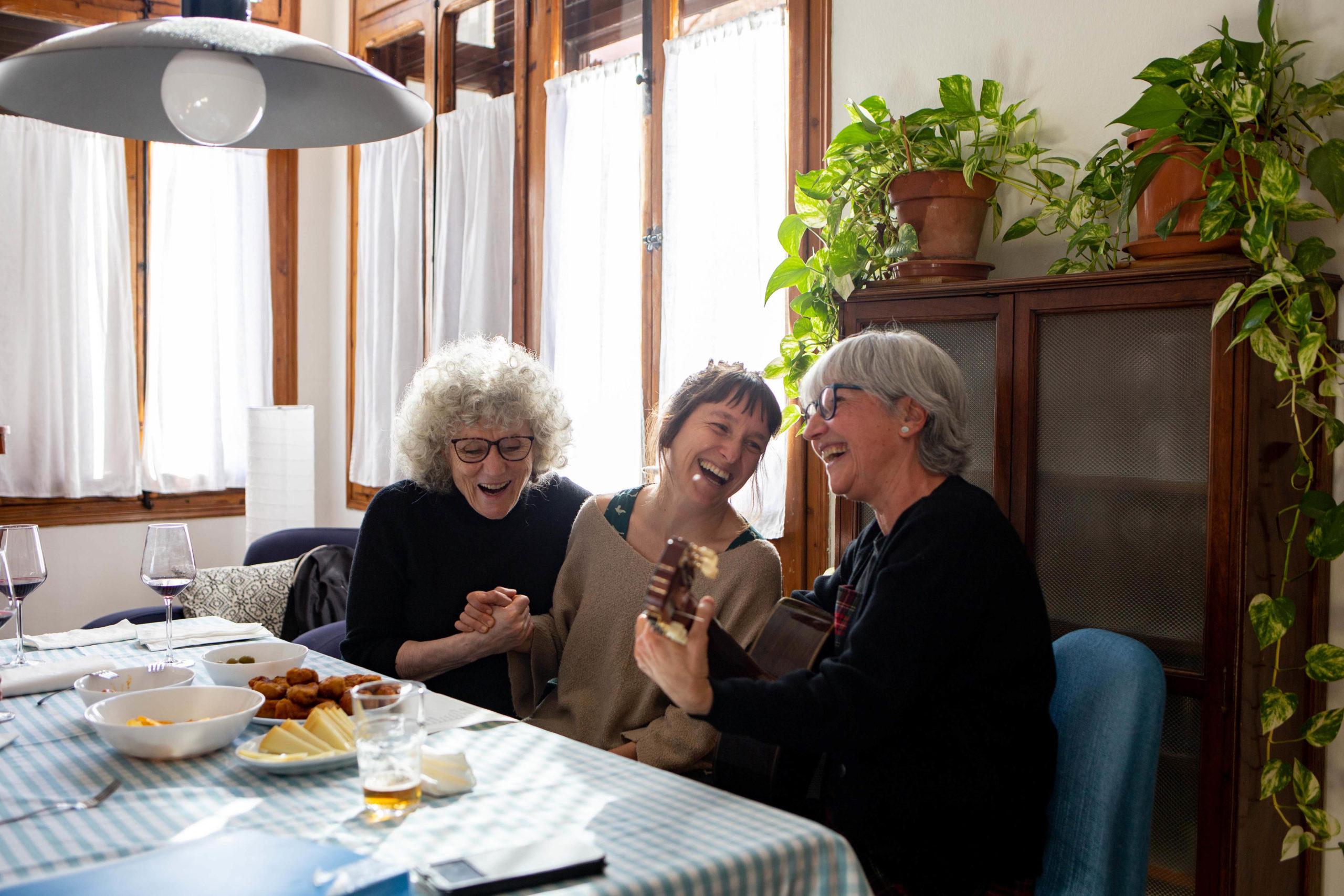 Tres amigues tocant la guitarra i rient al menjador de casa