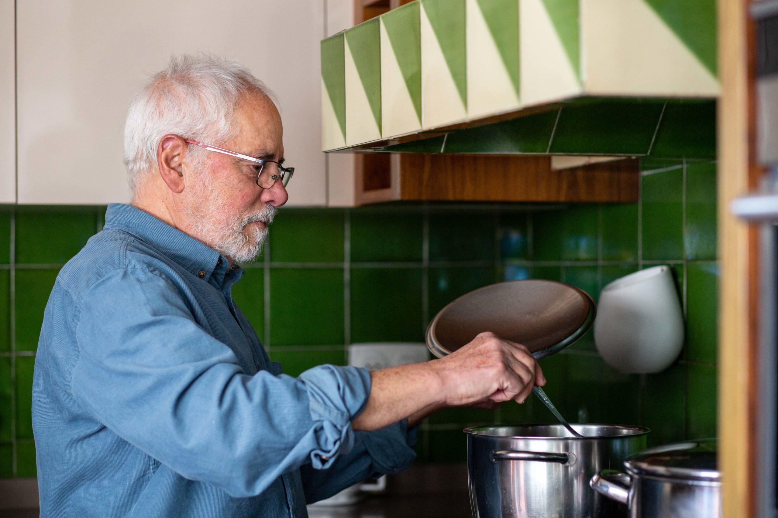 Home removent una olla a la cuina