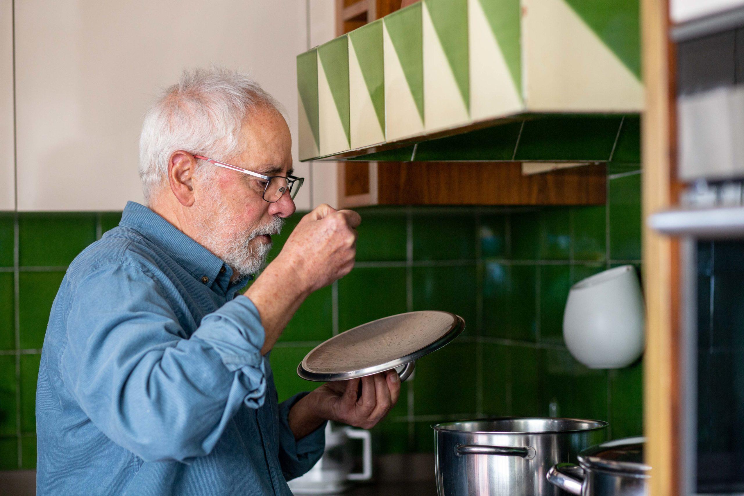 Home tastant el menjar d'una olla a la cuina