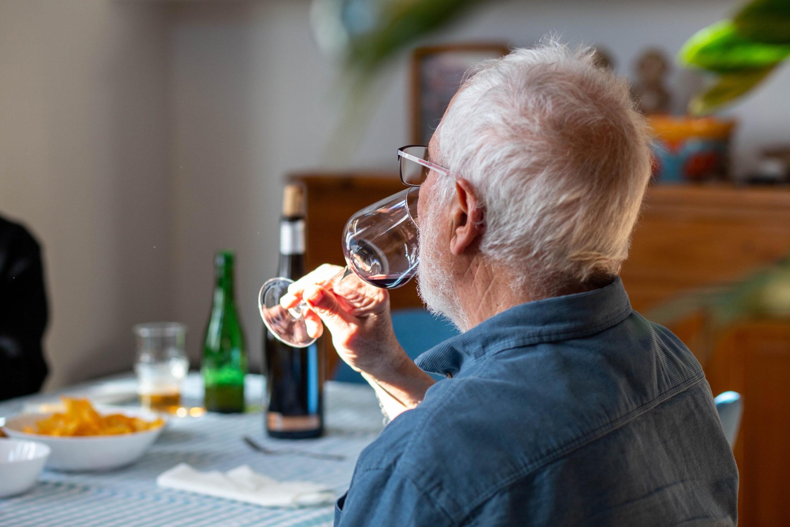 Home prenent una copa de vi en un dinar al menjador de casa