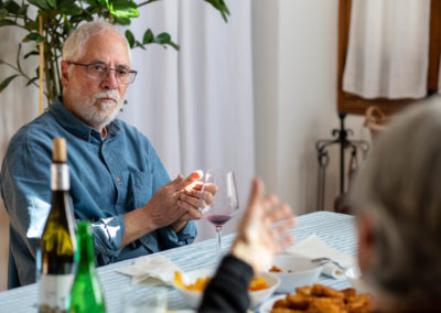 Home dinant amb amigues al menjador