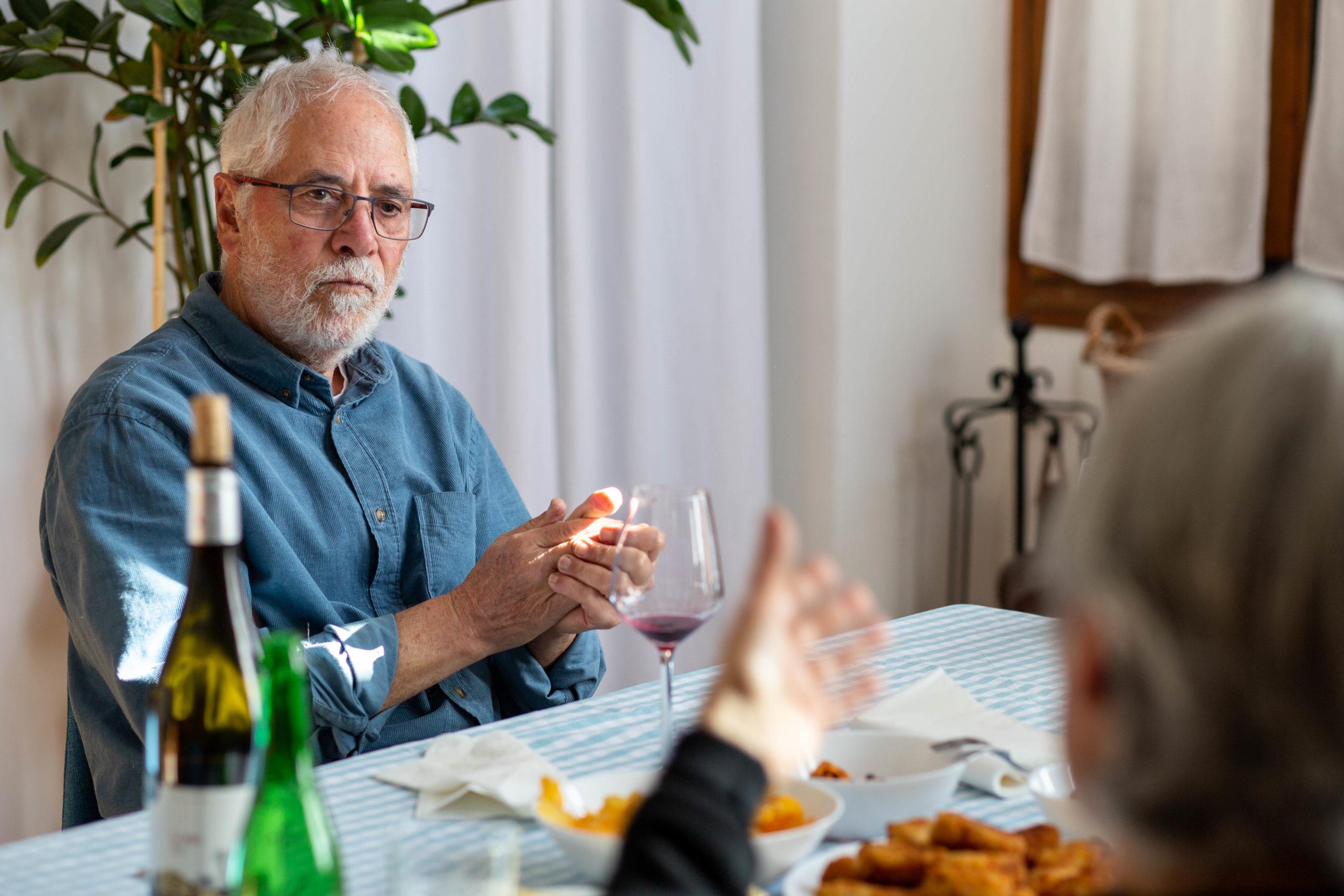 Home assegut en un dinar amb amigues al menjador de casa