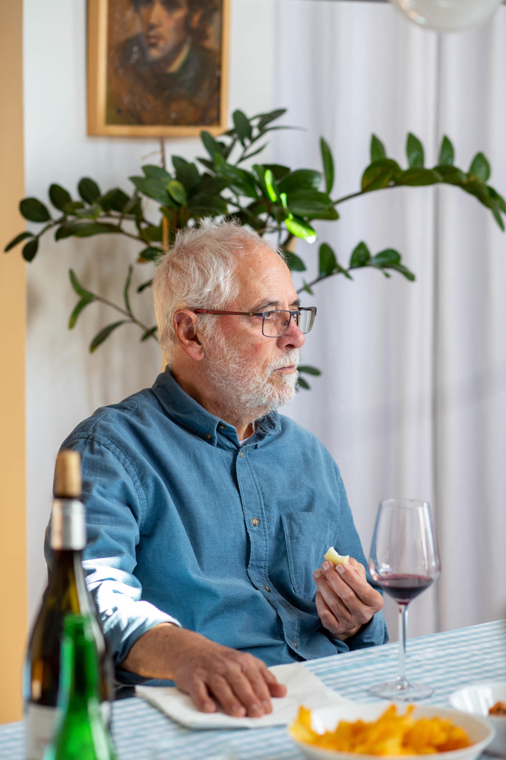 Home menjant assegut en un dinar al menjador de casa