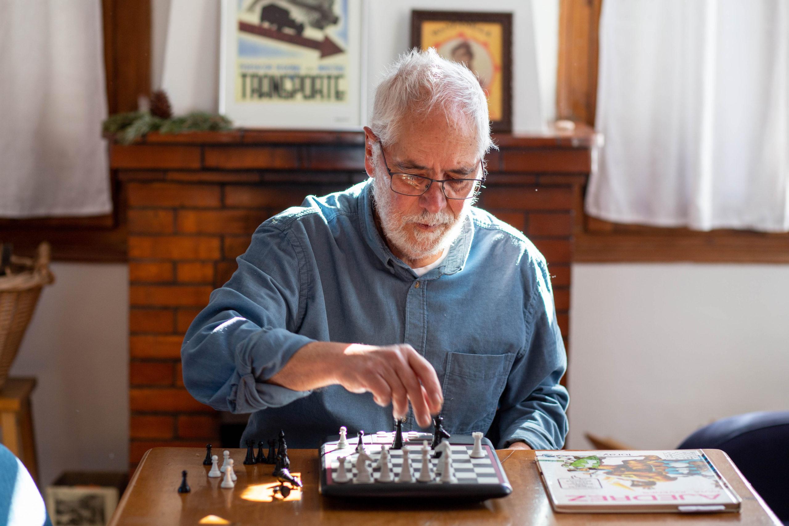Home assegut al menjador de casa jugant als escacs