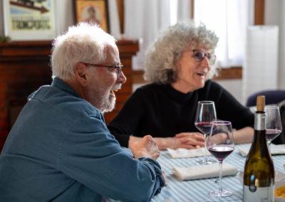Home assegut en un dinar amb amigues al menjador