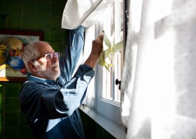 Home netejant vidres a la cuina de casa