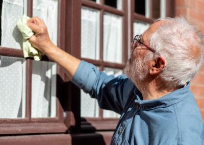 Home netejant vidres al pati de casa