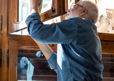 Home netejant vidres al menjador de casa