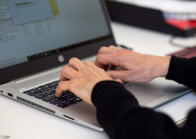 Pla detall mans de dona escrivint a l'ordinador