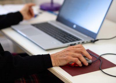 Pla detall mà de dona sobre ratolí i ordinador de fons