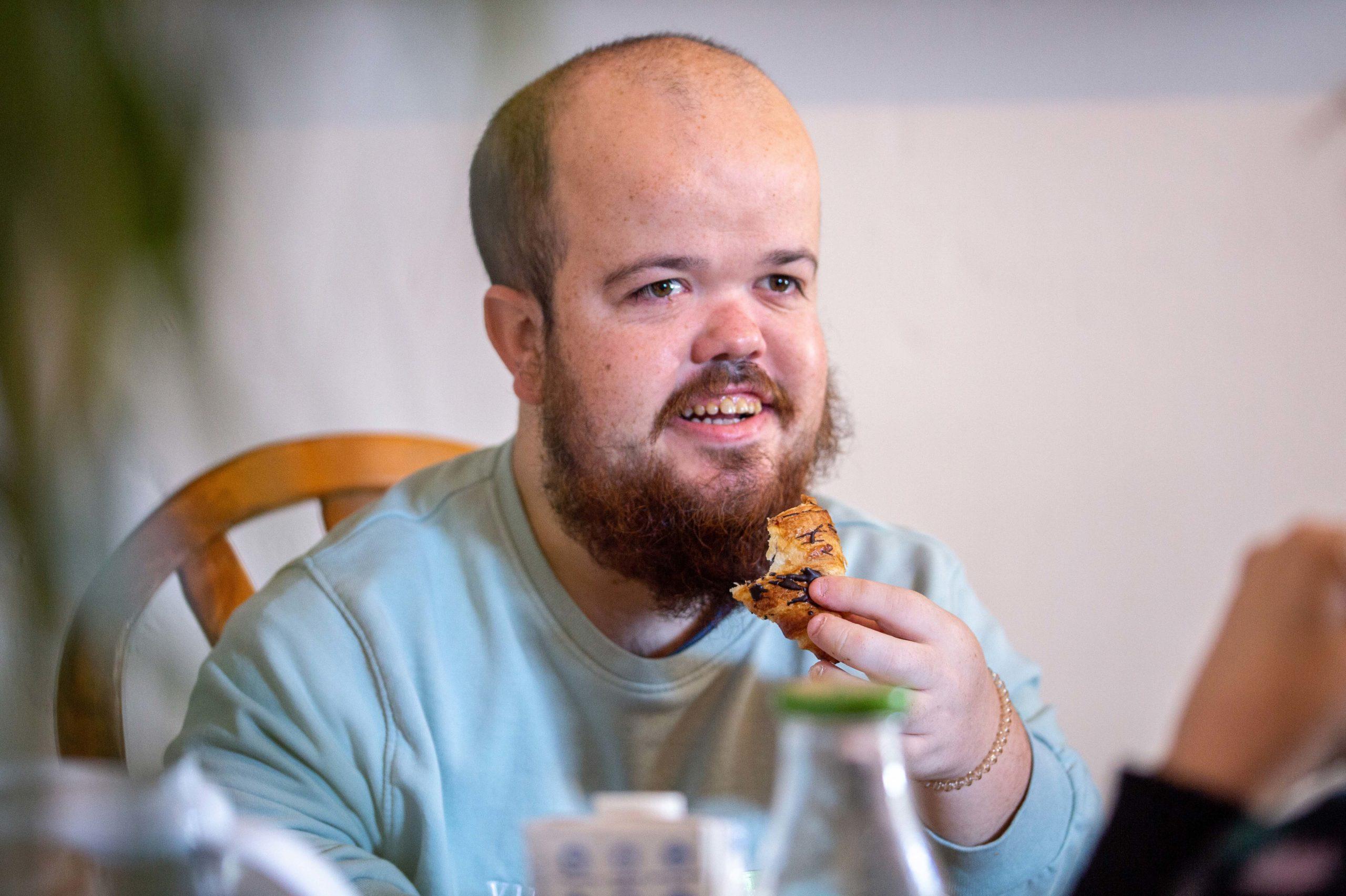 Un noi menjant un croissant al menjador